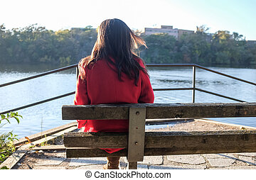 Woman sitting - Young woman sitting on a wooden chair next...