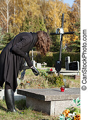 Widow at graveyard in fall - Widow in black putting red rose...