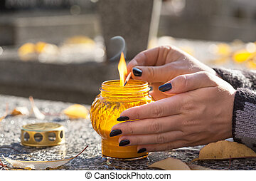 Lighting a candle - Woman at cemetery is lighting a yellow...