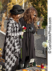 Women in mourning at cemetery in autumn - Two women standing...