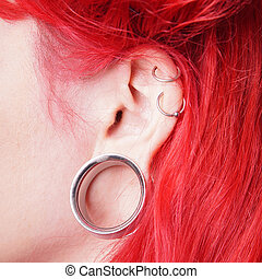flesh tunnel - stretched ear lobe piercing with flesh tunnel