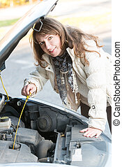 Woman checking oil level - Beautiful woman checking engine...