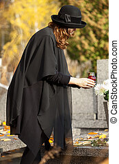Mother at cemetery in fall - Young mother holding a red...