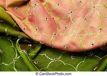 Pink and green satin textile background close up