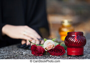 Loss of relative - Woman in mourning arranging flowers and...