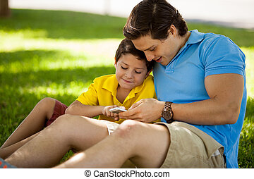 Father and son with a cell phone - Young father and his son...