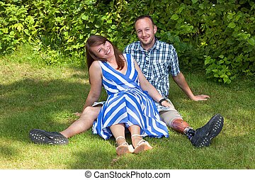 Happy attractive couple relaxing in the garden sitting close...