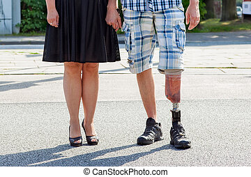 Male amputee wearing a prosthetic leg standing with a woman...