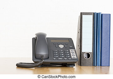 modern business phone with ring binder an folder on wooden...