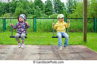 Young children, a boy with a girl swinging on a swing