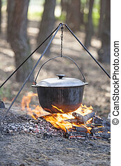 Campfire cooking - Camping kettle over burning campfire