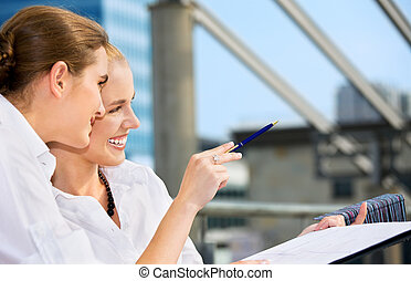 two happy businesswomen with paper chart focus on blonde