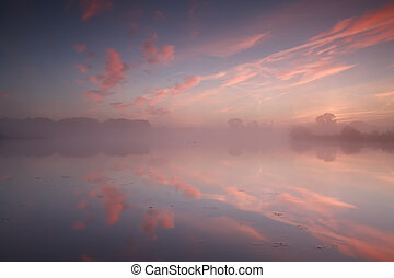 colorful misty sunrise over river