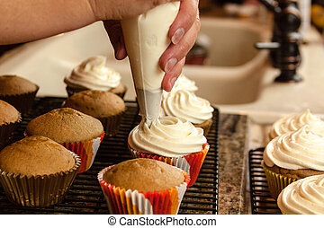 Baking Cupcakes - Female hands holding piping bag filled...