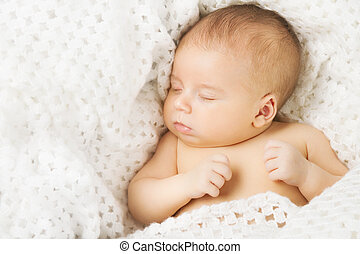 Baby newborn sleeping covered on white woollen blanket.