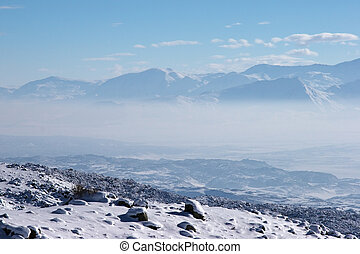 Fog in mountain valley in a sunny winter day