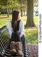 Woman sitting on bench - lonely young woman sitting on a...