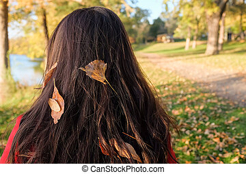Woman facing away - Young woman's hair with leafs waiting by...