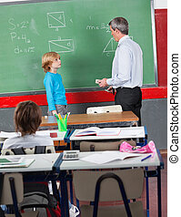 Schoolboy And Teacher Standing By Board In Classroom - Side...