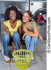 Female Friends Sitting Together Against Washing Machines