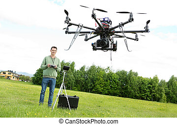 Technician Flying UAV Octocopter in Park - Happy young male...