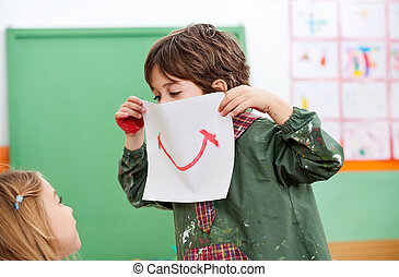 Boy Holding Paper With Smile Drawn On It - Playful little...
