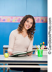 Teacher With Book Sitting At Desk In Classroom - Portrait of...