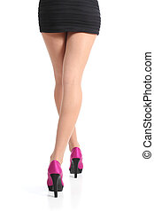 Back view of a woman legs walking with fuchsia high heels...