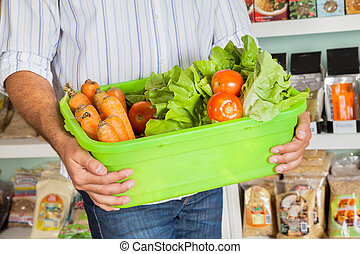Midsection Of Man Holding Vegetable Basket - Midsection of...