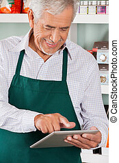 Owner Using Digital Tablet In Grocery Store - Happy senior...