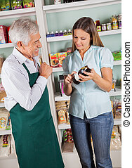 Senior Male Owner Assisting Female Customer In Choosing...