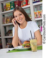 frau, knabberzeug, Telefon, während, gebrauchend, Haben, kaufmannsladen