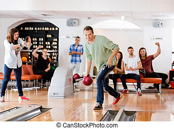 Man Bowling With Friends Cheering in Club - Young man...