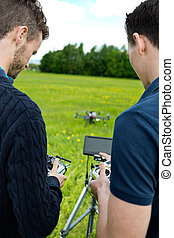 Engineers Operating UAV Helicopter - Rear view of young...