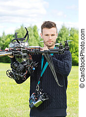 Male Engineer Holding UAV Helicopter in Park - Portrait of...