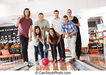 Woman Bowling While Friends Cheering in Club - Happy young...