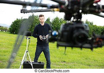 Engineer Flying UAV Helicopter in Park - Young male engineer...
