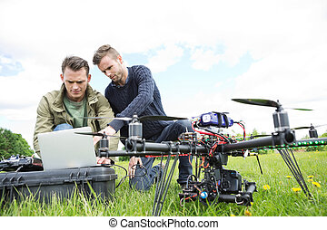 Engineers Using Laptop By UAV Octocopter - Young male...
