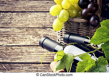 Bottles of red and white wine with fresh grape in basket