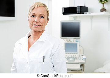Female Radiologist Standing In Examination Room