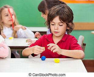 Boy Molding Clay At Classroom - Little boy molding clay with...