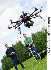 Engineers Operating UAV Octocopter in Park - UAV octocopter...