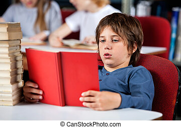 Relaxed Boy Reading Book At Table In Library - Relaxed...