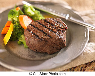 grilled steak on plate with vegetables