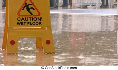 Caution wet floor, yellow sign by the pool