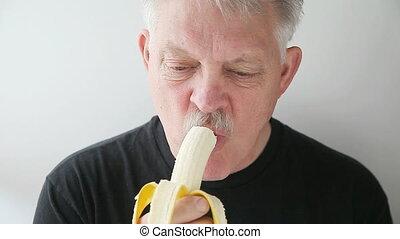 man eats banana - senior man eating fresh fruit