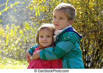 Brother hugging sister in autumn park