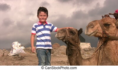 Boy with a camel - Child touching a camel and smiling at the...