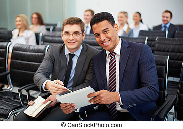 Business partners - Two happy young businessmen looking at...