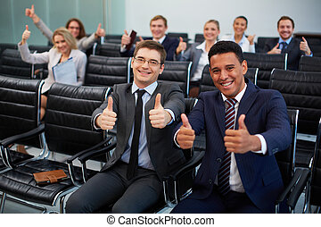 Competency - Two happy young businessmen showing thumbs up...